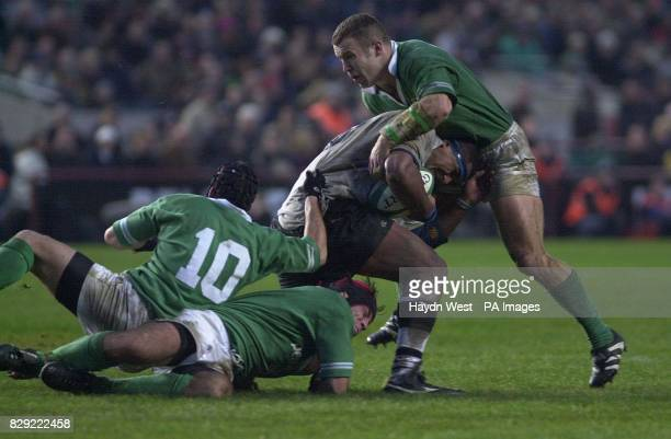 Ireland flanker Kieron Dawson holds on to the legs of Fiji lock Api Naevo with Irish outhalf David Humphreys and centre Kevin Maggs in the secondhalf...