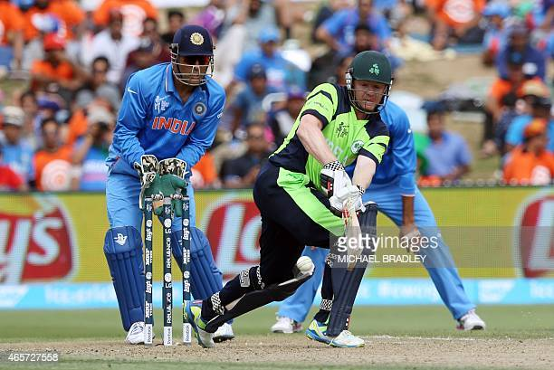 Ireland' Niall O'Brien hits a shot in front of India's MS Dhoni during the Pool B Cricket World Cup match between India and Ireland at Sedden Park in...
