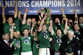 Ireland's centre Brian O'Driscoll celebrates with his teammates and the trophy after winning the Six Nations rugby union match between France and...