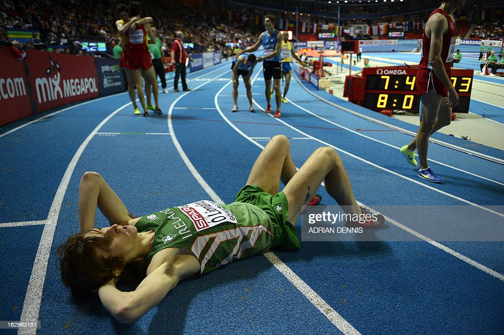Ireland's Ciarán O Lionáird (front) lies on the track after finishing third in the Men's 3000 metres event at the European Indoor athletics Championships in Gothenburg, Sweden, on March 2, 2013. AFP PHOTO / ADRIAN DENNIS