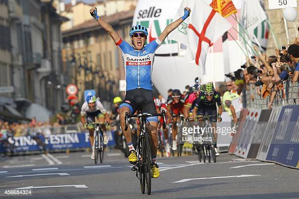 Ireland's Dan Martin of the Garmin team celebrates as he crosses the finnish line to win the 108th edition of the Giro di Lombardia cycling race from...