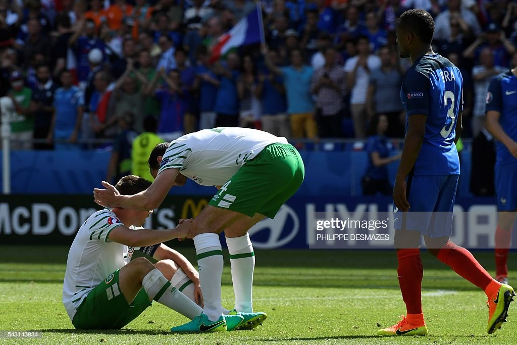 Ireland's defender Richard Keogh (L) is comforted by Ireland's defender John O'Shea next to France's defender Patrice Evra after the Euro 2016 round of 16 football match between France and Republic of Ireland at the Parc Olympique Lyonnais stadium in Décines-Charpieu, near Lyon, on June 26, 2016. France won the match 2-1. / AFP / PHILIPPE