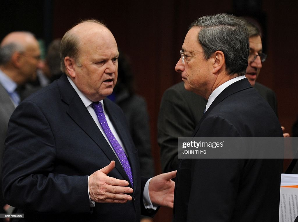 Ireland's Finance minister Michael Noonan (L) speaks with European Central Bank president Mario Draghi (R) before an Eurozone finance ministers meeting to decide on a fresh rescue loan for debt-stricken Greece, on November 20, 2012 at EU headquarters in Brussels. Greece has 'delivered' on reform and a deal will likely be clinched to unblock funds to keep it from bankruptcy, the head of the Eurogroup insisted despite a split with the IMF over how to get the stricken country's economic recovery on track.