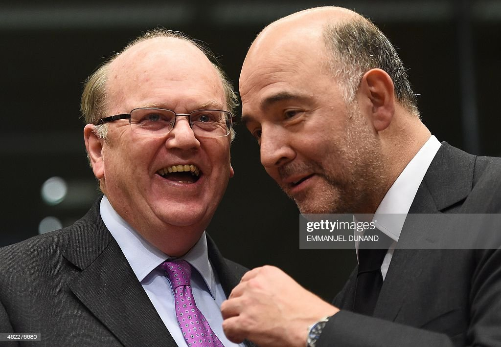 Ireland's Finance Minister Michael Noonan (L) speaks with European Commissioner for Economic and Financial Affairs, Taxation and Customs Pierre Moscovici at the start of an Eurogroup finance ministers meeting at the European Council in Brussels, January 26, 2015. AFP PHOTO/Emmanuel Dunand