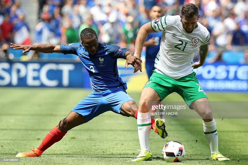 Ireland's forward Daryl Murphy and France's defender Patrice Evra vie for the ball during the Euro 2016 round of 16 football match between France and Republic of Ireland at the Parc Olympique Lyonnais stadium in Décines-Charpieu, near Lyon, on June 26, 2016. / AFP / Valery HACHE