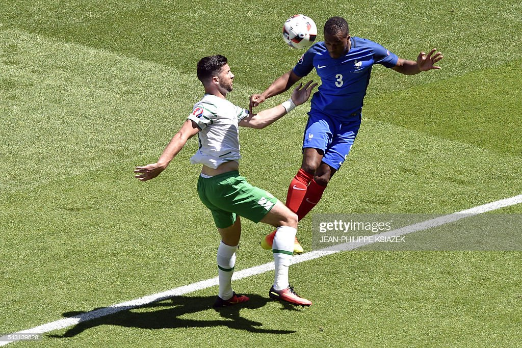 Ireland's forward Shane Long (L) and France's defender Patrice Evra vie for the ball during the Euro 2016 round of 16 football match between France and Republic of Ireland at the Parc Olympique Lyonnais stadium in Décines-Charpieu, near Lyon, on June 26, 2016. / AFP / JEAN