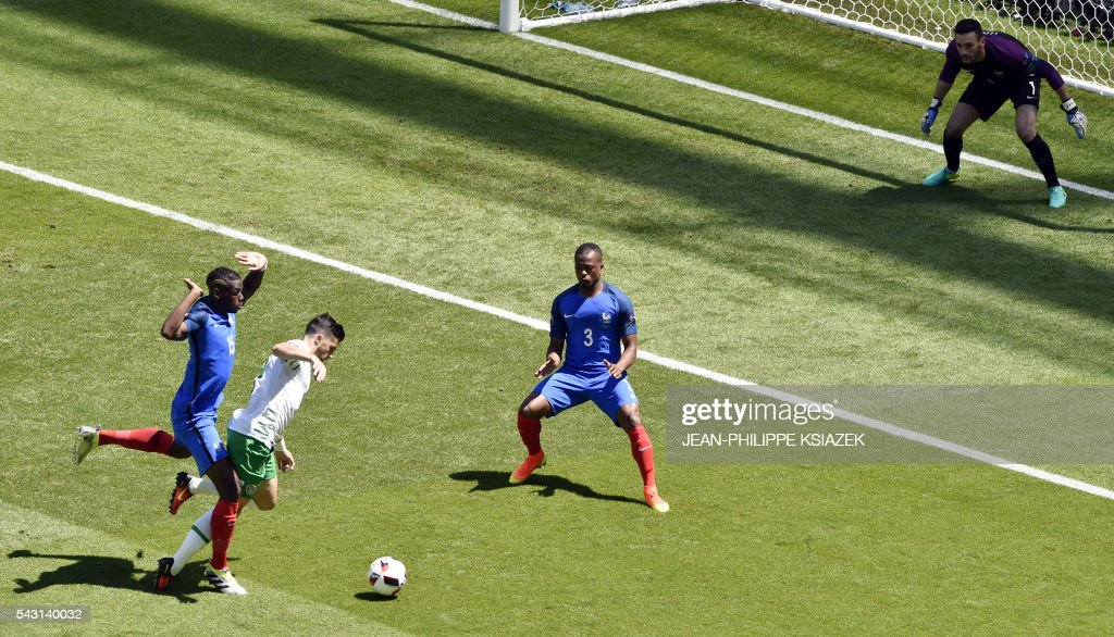 TOPSHOT - Ireland's forward Shane Long (2nd L) is challenged by France's midfielder Paul Pogba (L) during the Euro 2016 round of 16 football match between France and Republic of Ireland at the Parc Olympique Lyonnais stadium in Décines-Charpieu, near Lyon, on June 26, 2016. /