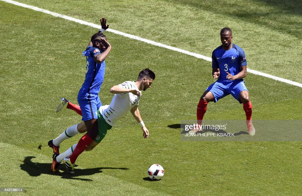 TOPSHOT - Ireland's forward Shane Long (C) is challenged by y France's midfielder Paul Pogba (L) as France's defender Patrice Evra (L) gestures during the Euro 2016 round of 16 football match between France and Republic of Ireland at the Parc Olympique Lyonnais stadium in Décines-Charpieu, near Lyon, on June 26, 2016. /