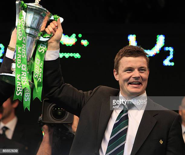 Ireland's historic Grand Slam winning team captain Brian O'Driscoll holds up the 6 Nations trophy as the team returns home to a hero's welcome at...