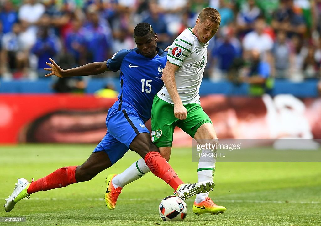 Ireland's midfielder James McCarthy (R) and France's midfielder Paul Pogba vie for the ball during the Euro 2016 round of 16 football match between France and Republic of Ireland at the Parc Olympique Lyonnais stadium in Décines-Charpieu, near Lyon, on June 26, 2016. / AFP / FRANCK