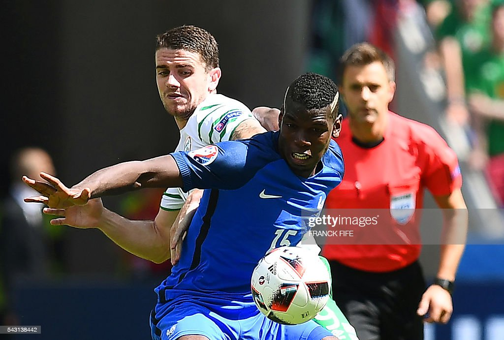 Ireland's midfielder Robert Brady (L) and France's midfielder Paul Pogba vie for the ball during the Euro 2016 round of 16 football match between France and Republic of Ireland at the Parc Olympique Lyonnais stadium in Décines-Charpieu, near Lyon, on June 26, 2016. / AFP / FRANCK