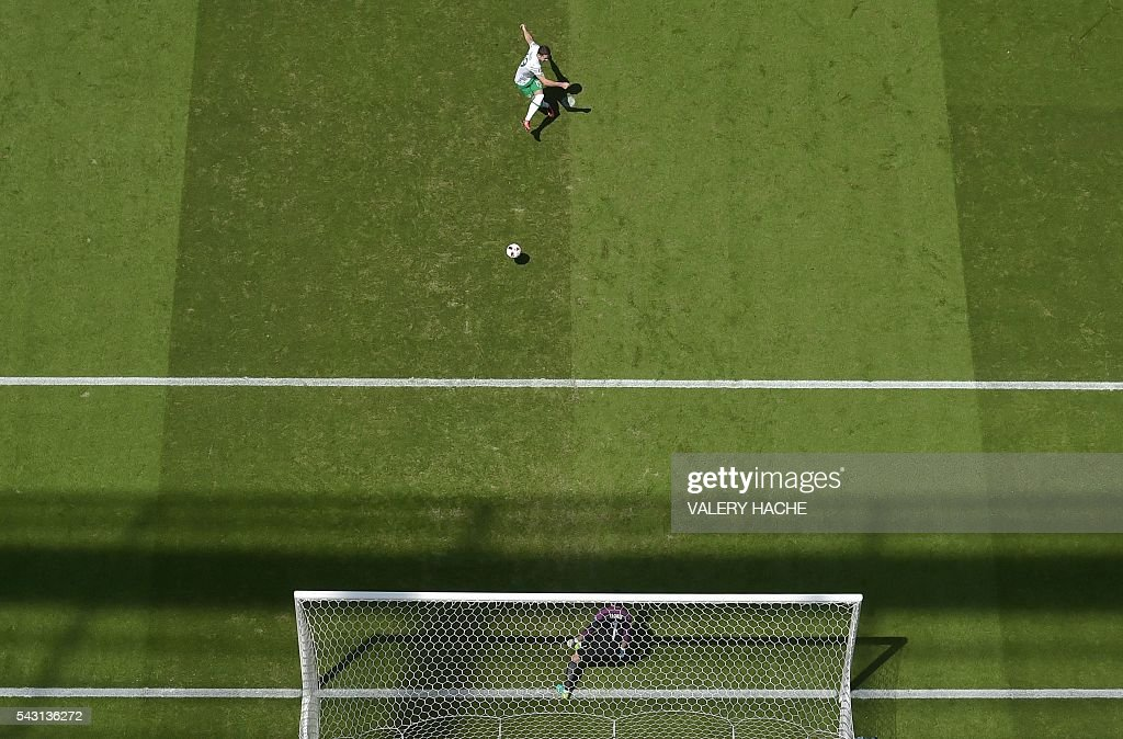 Ireland's midfielder Robert Brady (top) scores against France's goalkeeper Hugo Lloris during the Euro 2016 round of 16 football match between France and Republic of Ireland at the Parc Olympique Lyonnais stadium in Décines-Charpieu, near Lyon, on June 26, 2016. / AFP / Valery HACHE