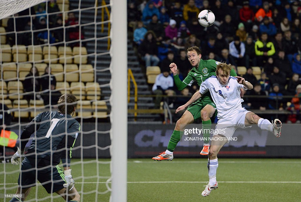 Ireland's national football player Aiden McGeady (C) vies with Faroe Islands' Simun Samuelsen (R) in front of Ireland's goalkeeper Keiren Westwood (L) during the FIFA 2014 World Cup group C qualifying football match Faroe Islands-Ireland on October 16, 2012 at the Torsvollur stadium in Torshavn on the Faroe Islands. NACKSTRAND