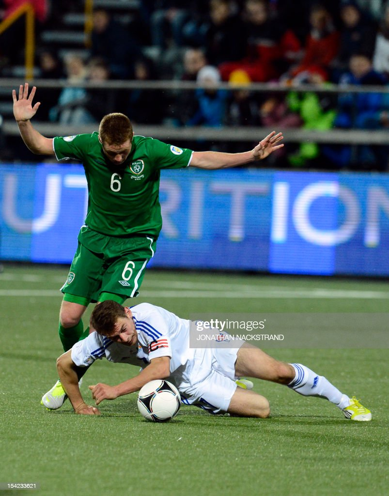Ireland's national team football player James McCarthy (L) vies with Faroe Islands's team captain Frodi Benjaminsen during the FIFA 2014 World Cup group C qualifying football match Faroe Islands vs Ireland at the Torsvollur stadium in Torshavn on October 16, 2012.
