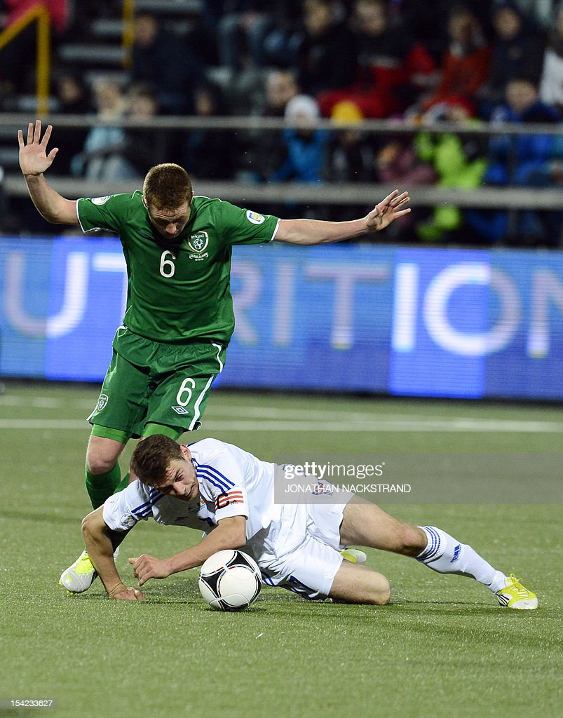 Ireland's national team football player James McCarthy (L) vies with Faroe Islands' team captain Frodi Benjaminsen during the FIFA 2014 World Cup group C qualifying football match Faroe Islands vs Republic of Ireland at the Torsvollur stadium in Torshavn on October 16, 2012.