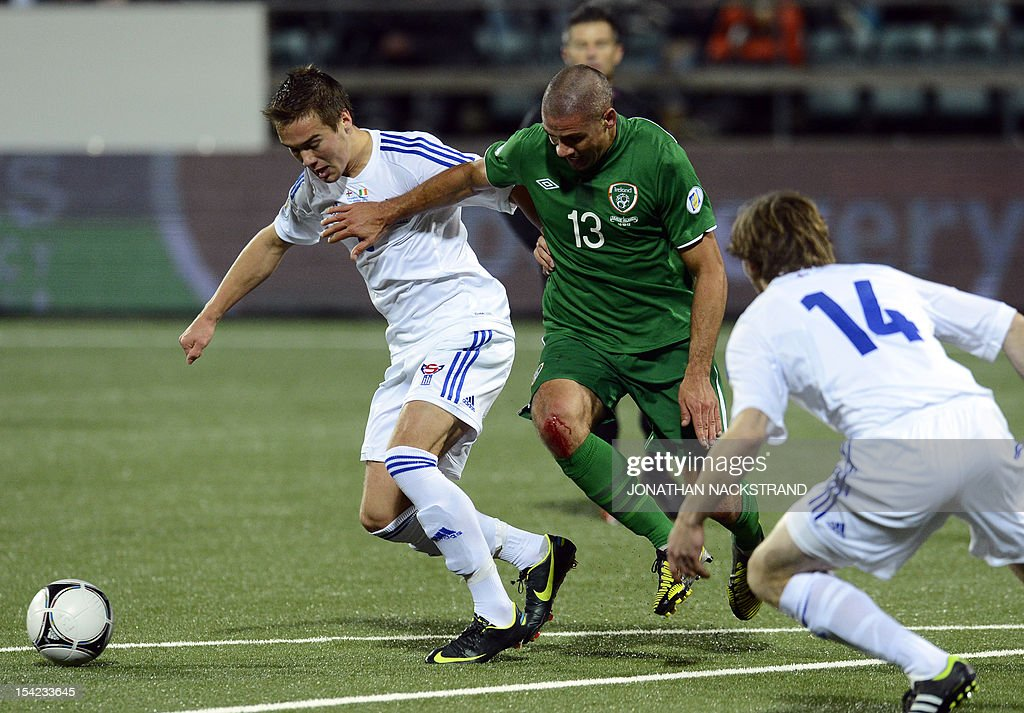 Ireland's national team football player Jon Walters (C) vies with Faroe Islands's Hallur Hansson (L) during the FIFA 2014 World Cup group C qualifying football match Faroe Islands vs Ireland at the Torsvollur stadium in Torshavn on October 16, 2012.