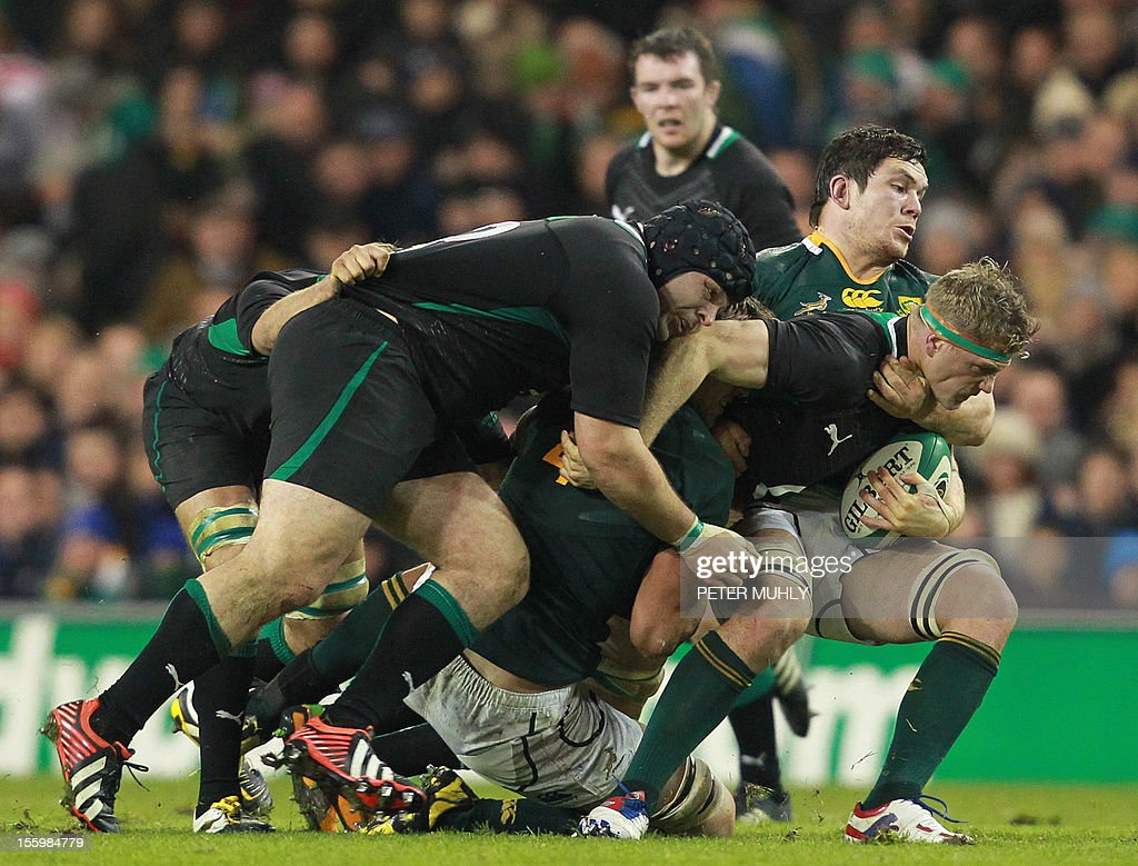 Ireland's Number 8 Jamie Heaslip (R) is tackled by South Africa's Willem Alberts (2nd R) during the Autumn International rugby union match between Ireland and South Africa at the Aviva stadium in Dublin, Ireland on November 10, 2012. AFP PHOTO/ PETER MUHLY