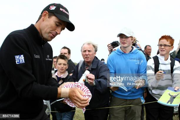 Ireland's Padraig Harrington smiles as a spectator offers some spray for his wrist during a practice round at the Royal Birkdale Golf Club Southport