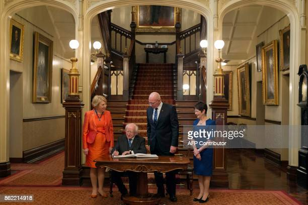 Ireland's President Michael Higgins signs a visitor's book as his wife Sabina New South Wales' Governor David Hurley and his wife Linda look on at...
