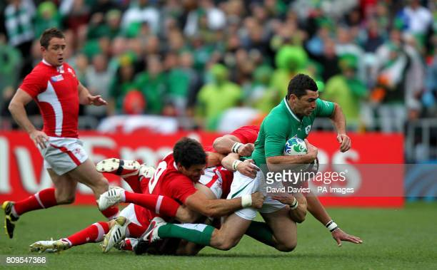 Ireland's Rob Kearrney is tackled by Wales' Mike Phillips and Toby Faletau during the 2011 Rugby World Cup Quarter Final match at the Wellington...