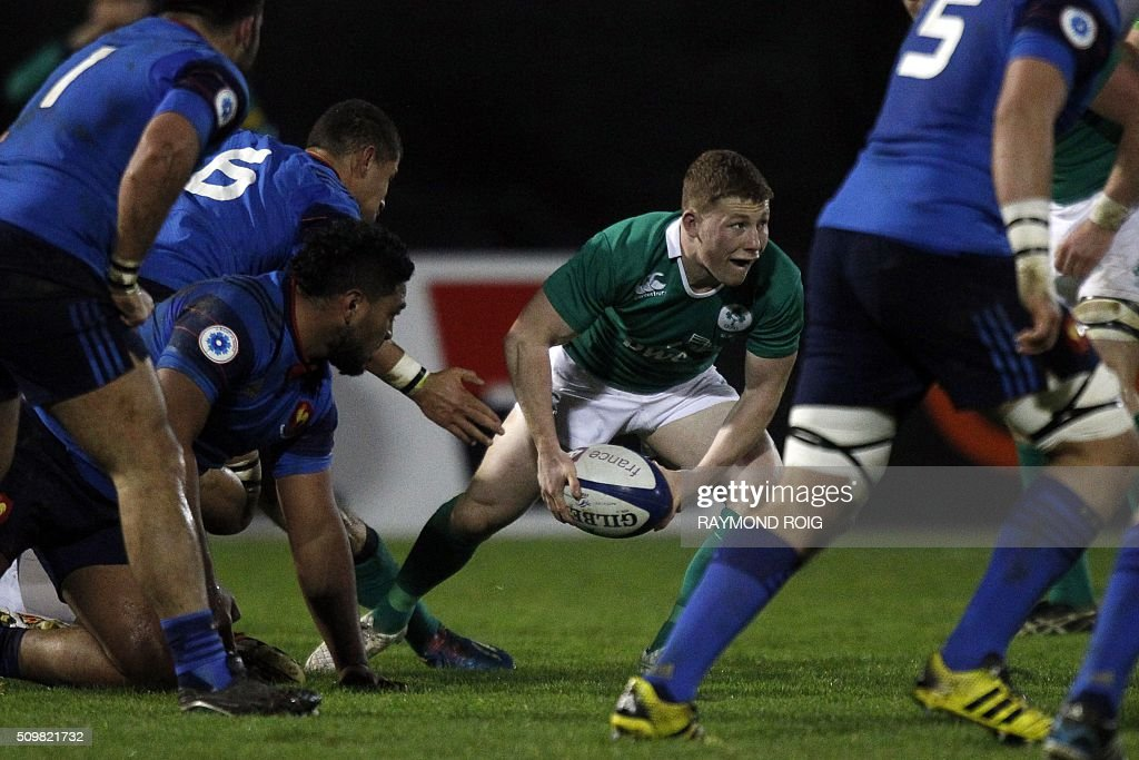 Ireland's scrum-half John Poland (C) passes the ball during the Under-20 Six Nations match France-Ireland in Narbonne, on February 12, 2016. / AFP / RAYMOND ROIG