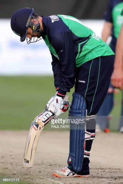 Ireland's Stuart Thompson inspects his bat after it broke when he hit a ball bowled by Australia's Patrick Cummings during the one day international...