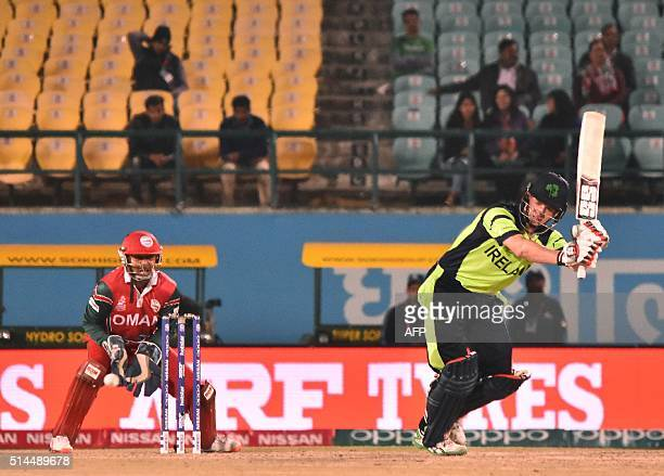 Ireland's William Porterfieldis watched by Oman's captain and wicketkeeper Sultan Ahmed as he plays a shot during the World T20 cricket tournament...