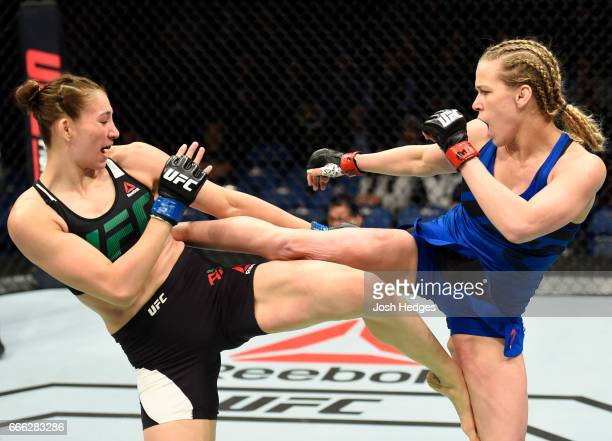 Irene Aldana of Mexico exchanges kicks with Katlyn Chookagian in their women's bantamweight bout during the UFC 210 event at KeyBank Center on April...