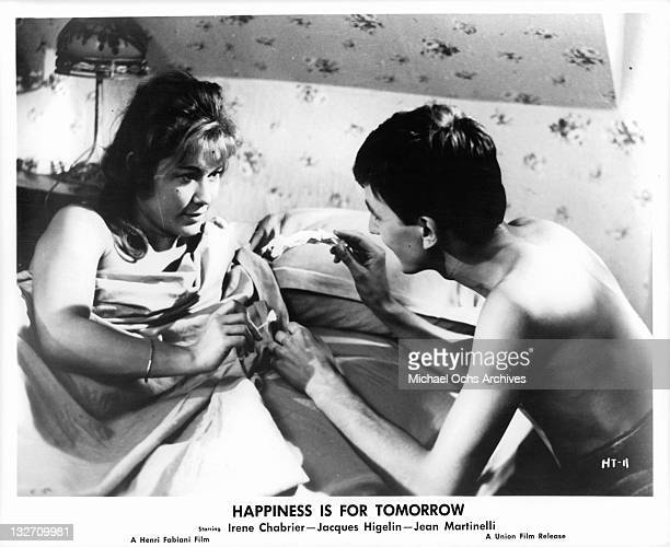 Irene Chabrier lighting piece of paper Jacques Higelin is holding on fire in a scene from the film 'Happiness Is For Tomorrow' 1961