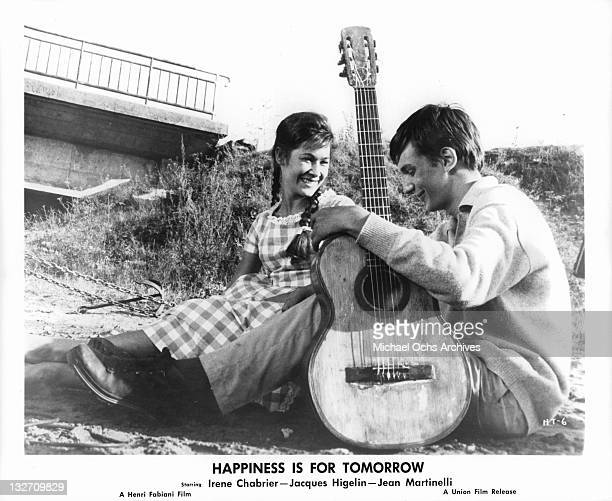 Irene Chabrier sitting on the sand with Jacques Higelin and and his guitar in a scene from the film 'Happiness Is For Tomorrow' 1961