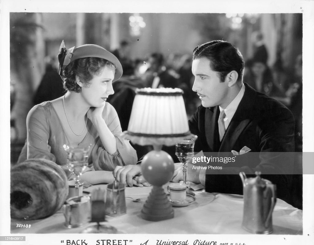 Irene Dunn and John Boles at a table in a scene from the film 'Back Street' 1932