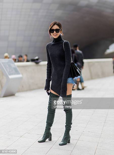 Irene Kim wearing a black navy grey sweater from Celine with long sleeves green overknees and denim shorts attends day 5 of HERA Seoul Fashion Week...