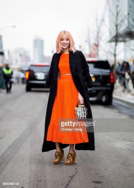 Irene Kim wearing an orange dress black coat outside Tory Burch on February 14 2017 in New York City