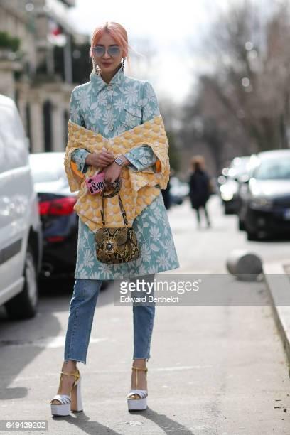 Irene Kim wears a flower print dress a snake print bag blue denim jeans and white shoes outside the Miu Miu show during Paris Fashion Week Womenswear...