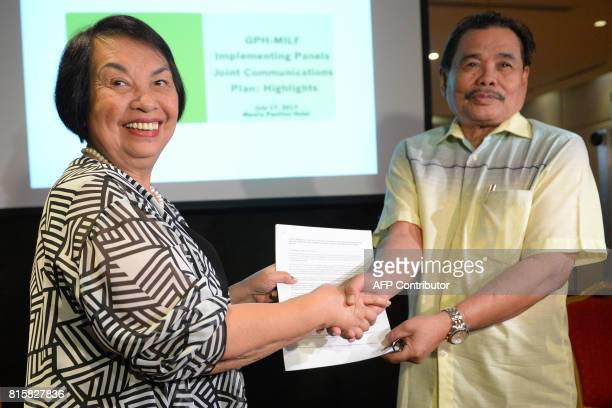 Irene Santiago chair of Philippine government's Implementing Panel for the Bangsamoro peace accords shakes hands with Moro Islamic Liberation Front...
