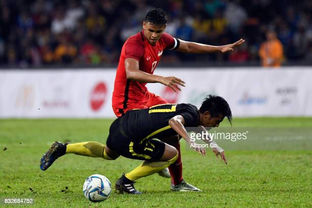 Irfan Fandi Ahmad of Singapore clashes Irfan Zakaria of Malaysia during the Men Fooball Group A compettion between Singapore and Malaysia at Shah...