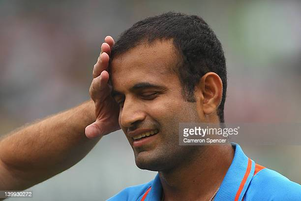 Irfan Pathan of India is checked by a trainer after colliding with team mate Suresh Raina during the One Day International match between Australia...