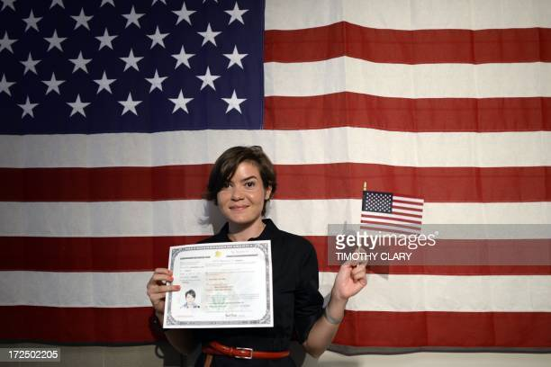 Irina Alexandra Tone holds her new citizenship documents following a naturalization ceremony July 2 2013 in New York 150 immigrants as part of...