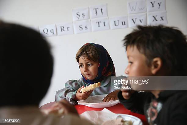 Irina and other Roma children eat bread and ham during snacktime at a preschool class in the abjectly poor Roma settlement of Ponorata on September...
