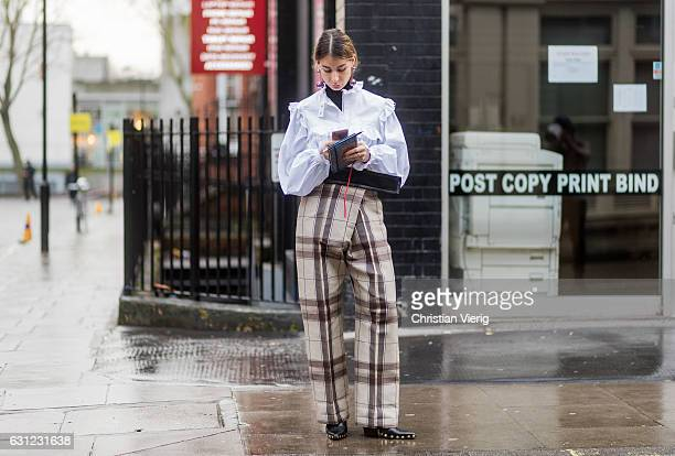 Irina Lakicevic wearing a white blouse checked pants during London Fashion Week Men's January 2017 collections at JW Anderson on January 8 2017 in...