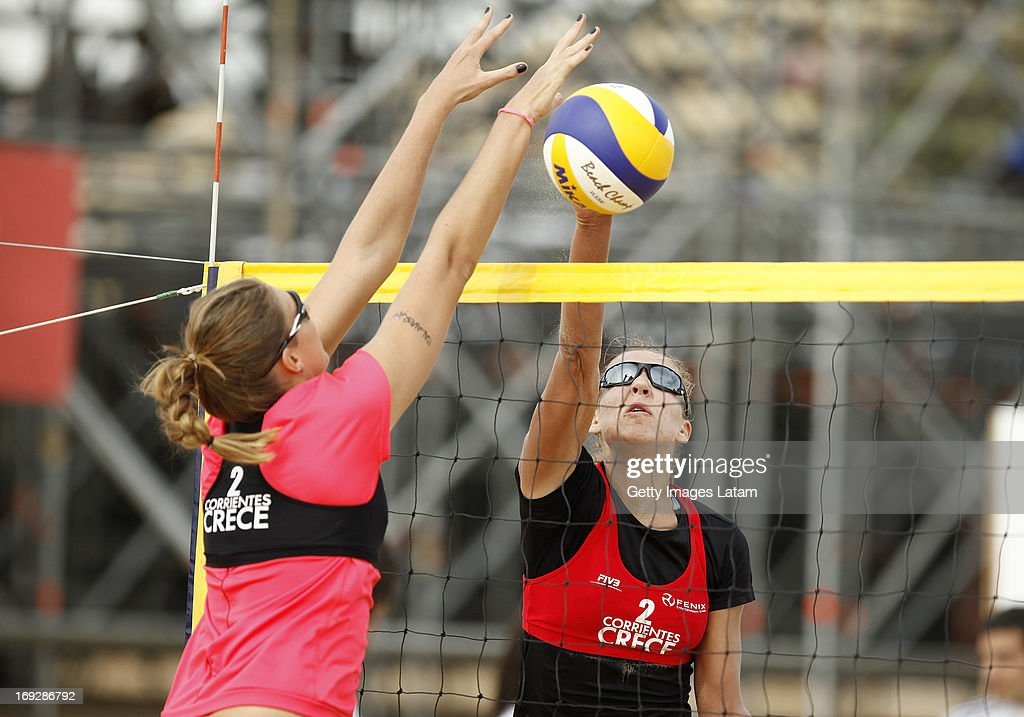 Irina Tsimbalova (in Red) of Kazakstan smashes the ball as Nina Grawender (in black) of Sweden tries to block during a match between Kazakstan and Swede as part of day one of Corrientes Grand Slam of FIVB World Tour at Arazaty Beach on May 22, 2013 in Corrientes, Argentina.