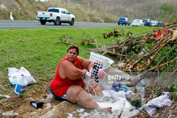 TOPSHOT Iris Vazquez washes clothing at an open road drainage next to a road in Corozal west of San Juan Puerto Rico on September 24 2017 following...