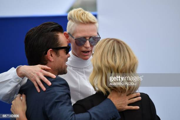 Irish actor Colin Farrell British actress Tilda Swinton and South AfricanUS actress Charlize Theron embrace on May 23 2017 within a photocall for the...