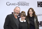 Irish actor Liam Cunningham British actress Maisie Williams and Dutch actress Carice van Houten pose during the opening of the exhibition about the...