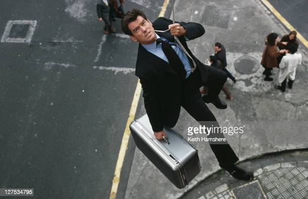 Irish actor Pierce Brosnan leaps from a banker's window carrying a briefcase in the opening scene of the James Bond film 'The World Is Not Enough'...