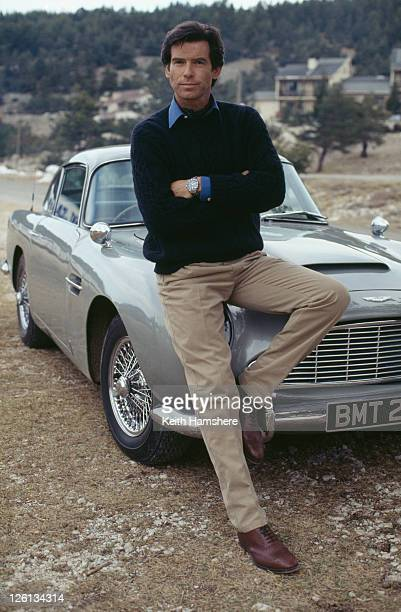 Irish actor Pierce Brosnan poses against an Aston Martin DB5 in a publicity still for the James Bond film 'GoldenEye' 1995