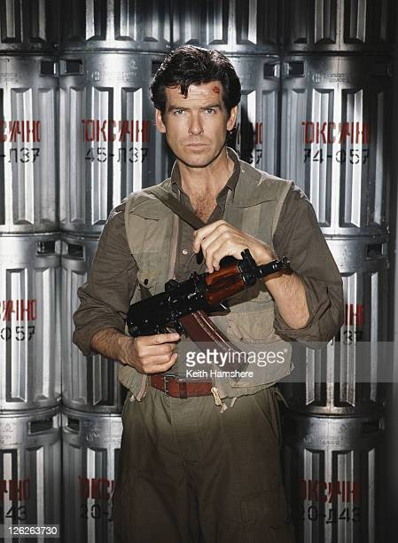 Irish actor Pierce Brosnan stars as James Bond in the film 'GoldenEye' 1995 Here he poses against several barrels of Russian toxic chemicals whilst...