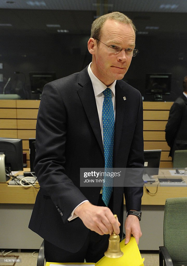 Irish agriculture marine and food minister Simon Coveney rings the bell before an Agriculture and Fisheries Council meeting at the EU Headquarters in Brussels on February 26, 2013.