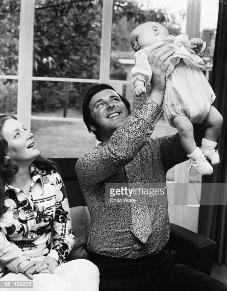 Irish broadcaster Terry Wogan with his wife Helen holding his baby daughter Katherine in the air at their home circa 1972