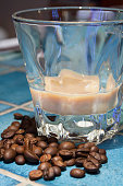 Irish Cream - coffee - chocolate liqueur in a glass served with coffee beans on the bar - table with blue ceramic tiles.